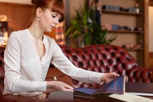 Female tailor browsing fabric in menswear shopの写真素材 [FYI02173832]