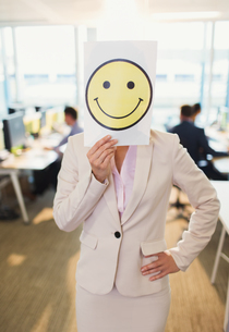 Portrait of businesswoman holding smiley face printout over her face in officeの写真素材 [FYI02173845]
