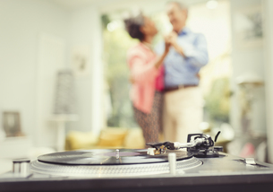 Mature couple dancing in living room behind record playerの写真素材 [FYI02173854]