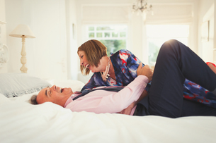 Well-dressed mature couple laughing on bedの写真素材 [FYI02173860]