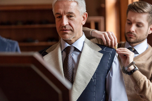Tailor fitting businessman for suit in menswear shopの写真素材 [FYI02173874]