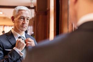 Businessman trying on tie in mirror in menswear shopの写真素材 [FYI02173885]