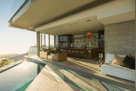 Sunny luxury home showcase exterior patio with infinity poolの写真素材 [FYI02173901]
