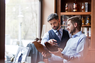 Businessmen examining dress shoes in menswear shopの写真素材 [FYI02173905]