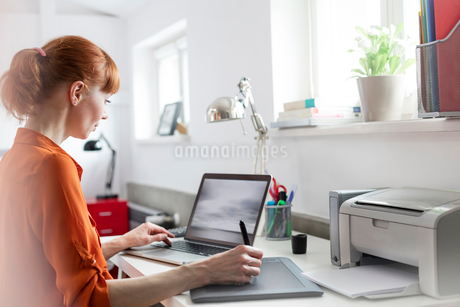 Designer using graphics tablet at laptop in officeの写真素材 [FYI02173926]