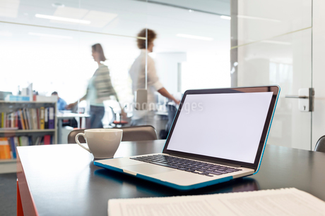 Laptop and coffee cup on desk with business people walking in backgroundの写真素材 [FYI02173975]