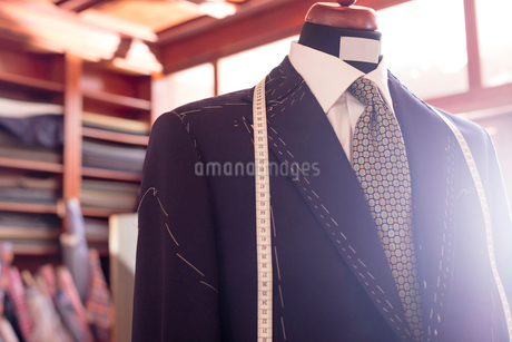 Close up tailored suit and tape measure on dressmakers model in menswear shopの写真素材 [FYI02173985]