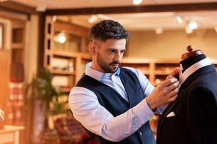 Tailor adjusting tie on dressmakers model in menswear shopの写真素材 [FYI02174027]