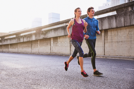 Runner couple running on urban streetの写真素材 [FYI02174037]