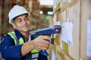 Worker with scanner scanning barcode on box in distribution warehouseの写真素材 [FYI02174042]