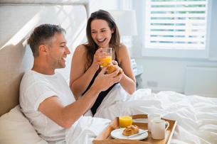 Smiling couple enjoying breakfast in bedの写真素材 [FYI02174075]