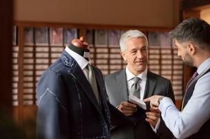 Tailor explaining suit to businessman in menswear shopの写真素材 [FYI02174091]