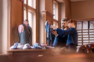Worker showing ties to businessman in menswear shopの写真素材 [FYI02174097]
