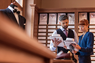 Worker showing businessman dress shirts in menswear shopの写真素材 [FYI02174123]