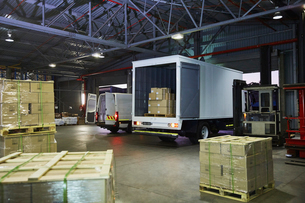 Trucks and cardboard box pallets at distribution warehouse loading dockの写真素材 [FYI02174133]