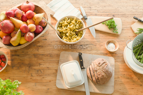 Overhead view pasta, fruit and bread on dining tableの写真素材 [FYI02174176]