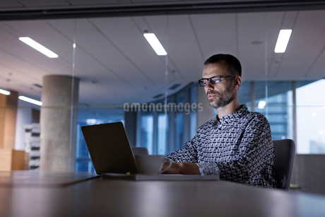 Businessman working late at laptop in officeの写真素材 [FYI02174228]