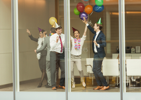 Business people wearing party hats and dancing with balloons at conference room windowの写真素材 [FYI02174267]
