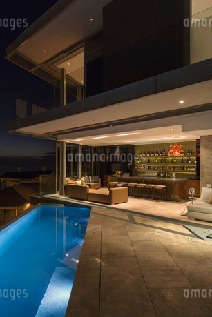 Illuminated luxury home showcase bar and patio with lap pool at nightの写真素材 [FYI02174281]
