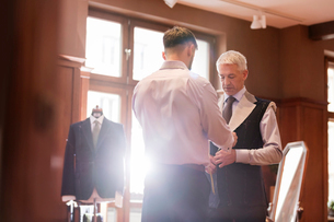 Tailor fitting businessman for suit in menswear shopの写真素材 [FYI02174337]