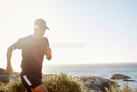 Male triathlete runner running along oceanの写真素材 [FYI02174356]