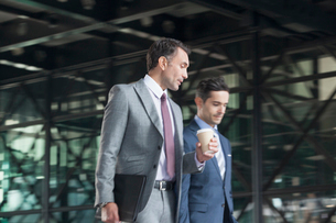 Corporate businessmen with coffee talking and walkingの写真素材 [FYI02174401]