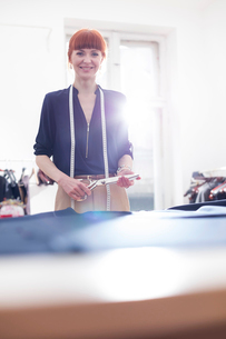 Portrait confident female tailor holding scissors in menswear workshopの写真素材 [FYI02174406]