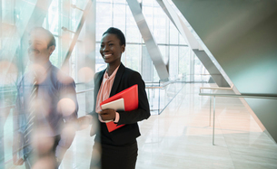 Smiling corporate businesswoman in modern office lobbyの写真素材 [FYI02174416]