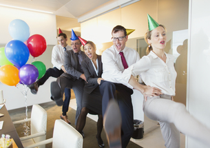 Playful business people with party hats dancing in conga lineの写真素材 [FYI02174440]