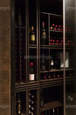 Wine bottles organized on wooden shelves in wine libraryの写真素材 [FYI02174474]