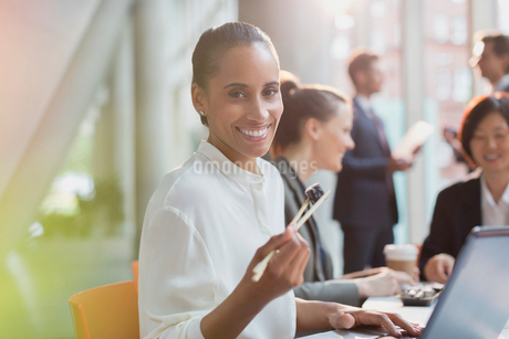 Portrait smiling businesswoman eating sushi lunch with chopsticks in conference room meetingの写真素材 [FYI02174477]