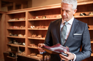 Businessman shopping for dress shoes in menswear shopの写真素材 [FYI02174487]