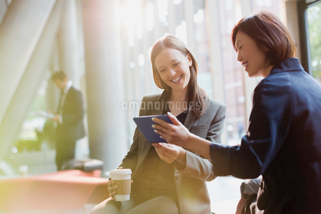 Businesswomen drinking coffee and using digital tablet in office lobbyの写真素材 [FYI02174489]
