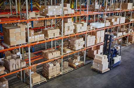 Worker operating forklift moving cardboard boxes along distribution warehouse shelvesの写真素材 [FYI02174508]