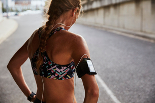 Fit female runner in sports bra with mp3 player armband and headphones resting on urban streetの写真素材 [FYI02174519]