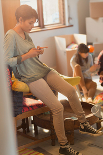 Young woman texting with cell phone in new apartmentの写真素材 [FYI02174541]
