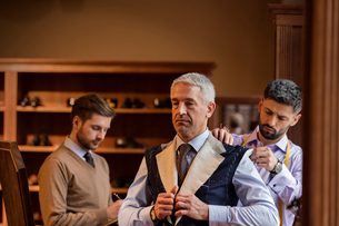 Tailors fitting businessman for suit in menswear shopの写真素材 [FYI02174591]