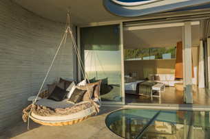 Hanging cushion bed on sunny modern luxury home showcase patioの写真素材 [FYI02174597]