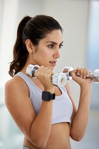 Focused brunette woman doing biceps hammer curls with dumbbellsの写真素材 [FYI02174645]