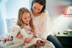 Mother reading bedtime story with daughter in bedの写真素材 [FYI02174647]