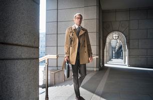 Corporate businessman in trench coat walking in cloisterの写真素材 [FYI02174692]