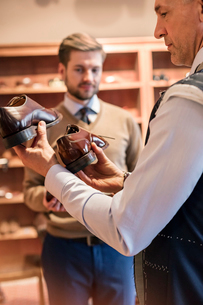 Businessman shopping for dress shoes in menswear shopの写真素材 [FYI02174700]