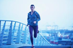 Female runner running on urban footbridge at dawnの写真素材 [FYI02174718]