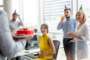 Business people celebrating birthday with cake in officeの写真素材 [FYI02174728]