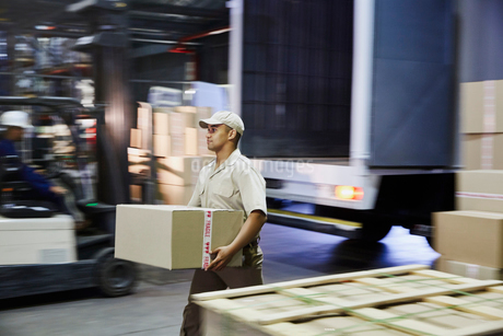 Worker carrying cardboard box at distribution warehouse loading dockの写真素材 [FYI02174765]