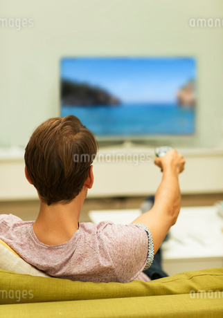 Man watching TV changing channels on living room sofaの写真素材 [FYI02174800]