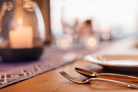 Close up illuminated candle and placesetting on dining tableの写真素材 [FYI02174813]