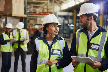 Workers with clipboard talking in distribution warehouseの写真素材 [FYI02174834]
