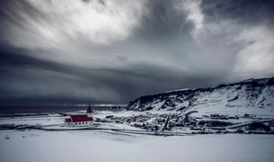 Church in remote snow covered landscape below stormy sky, Vik, Icelandの写真素材 [FYI02174913]