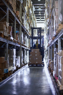 Worker driving forklift with cardboard boxes in aisle of distribution warehouseの写真素材 [FYI02174940]
